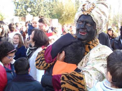 El director general vestido de Baltasar abraza a un alumno del María Auxiliadora